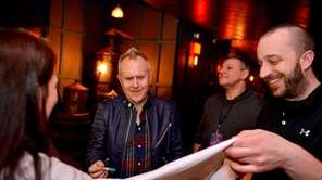 Musician Howard Jones, center left, signs a t-shirt