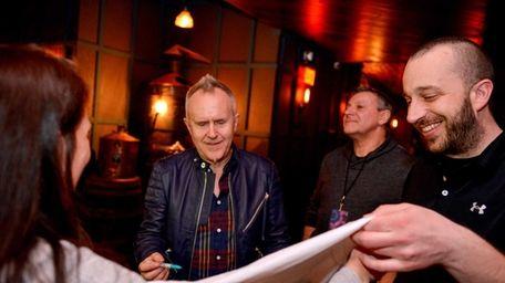Musician Howard Jones, center left, signs a t-shirt