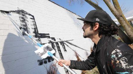 Muralist Karlito Miller-Espinosa, known as Mata Ruda, paints