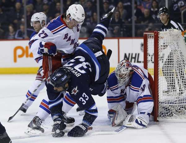 Winnipeg Jets' Dustin Byfuglien gets checked by New