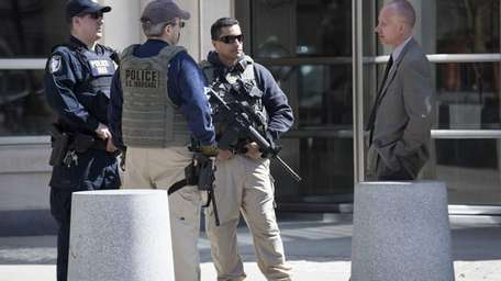 Armed authorities stand outside federal court in Brooklyn