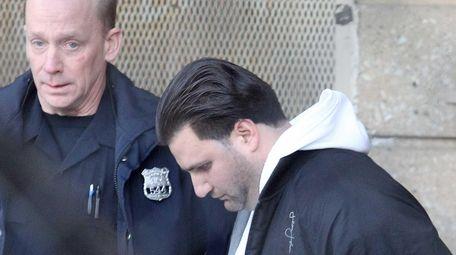 Andrew A. Quattrone, 32, of Lindenhurst, is escorted