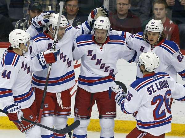 New York Rangers' Dominic Moore, center, is congratulated