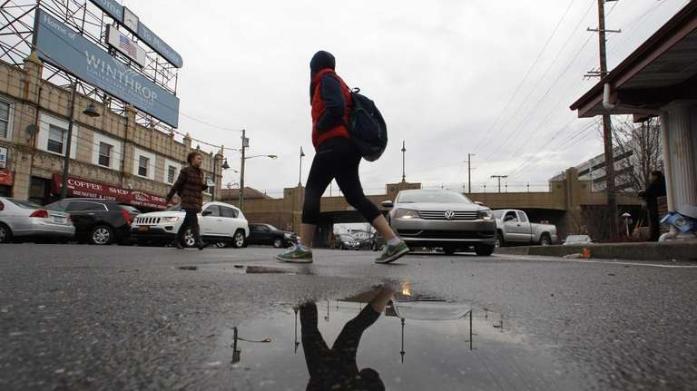 Pedestrians dodge puddles on Station Plaza North as