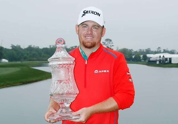 J. B. Holmes poses with the trophy after