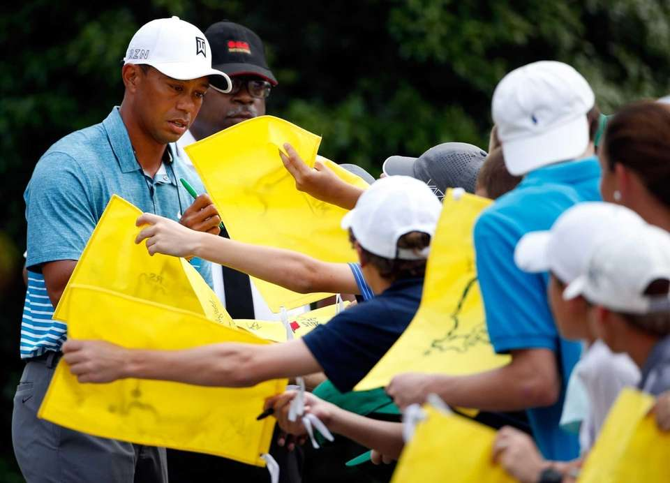 Tiger Woods signs his autograph for a patron