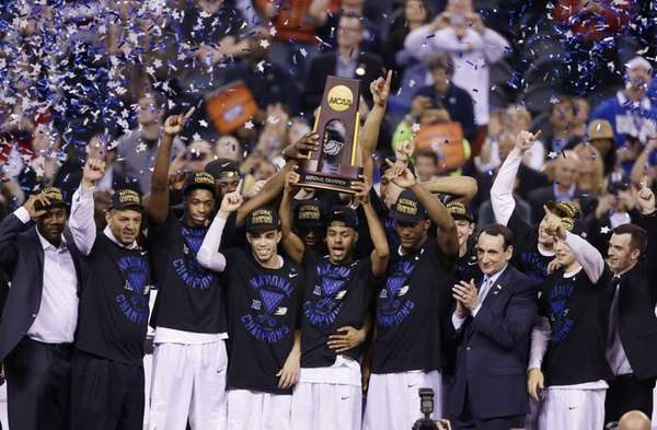 Duke players celebrate with the trophy after their