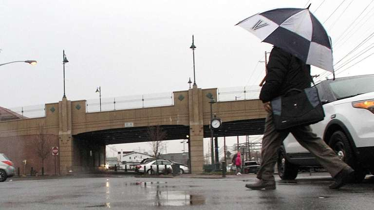 Pedestrians walk through the rain on Station Plaza