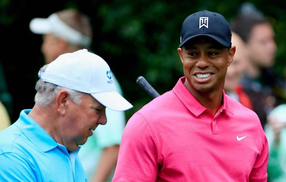Mark O'Meara, left, walks alongside Tiger Woods during