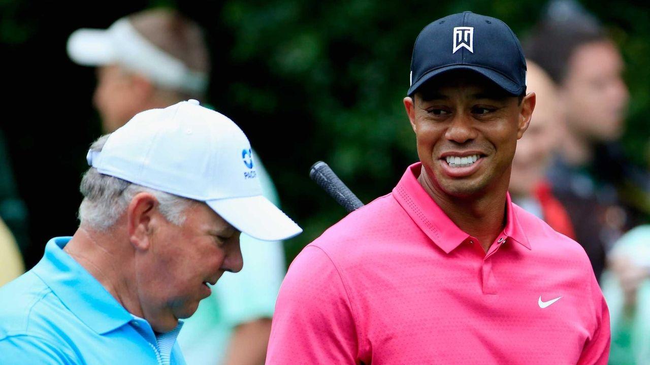 Mark O'Meara, left, walks alongside Tiger Woods during