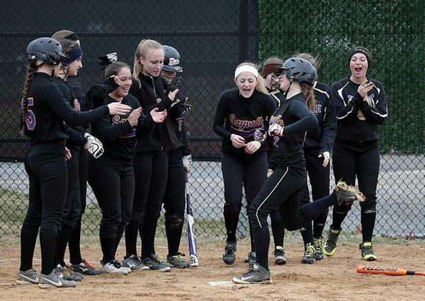 Teammates cheer shortstop Lyndsey Shaw at home after