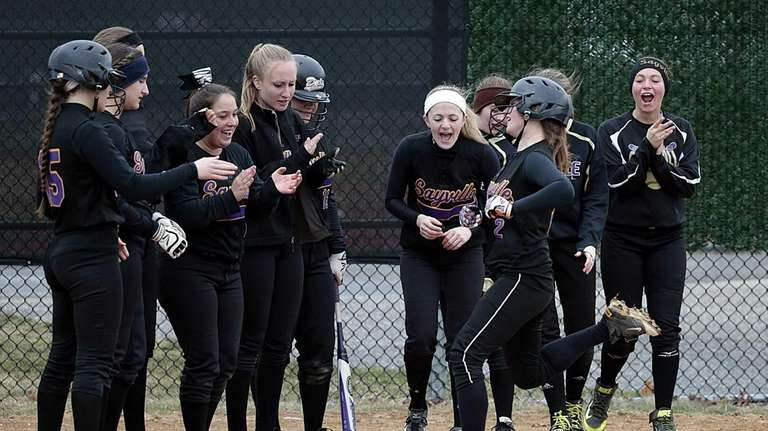 Teammates cheer shortstop Lyndsey Shaw at home after