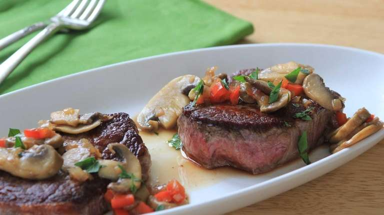 Filet mignon steaks are seared and topped with