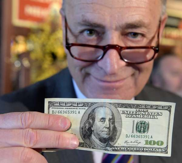 Sen. Charles Schumer holds up a counterfeit $100
