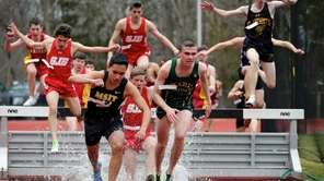 Runners jump over the water barrier as they
