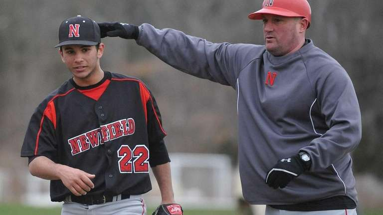 Newfield pitcher Brandon Alberto, right, gets a pat