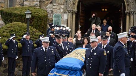 Firefighters carry the casket of volunteer firefighter Robert