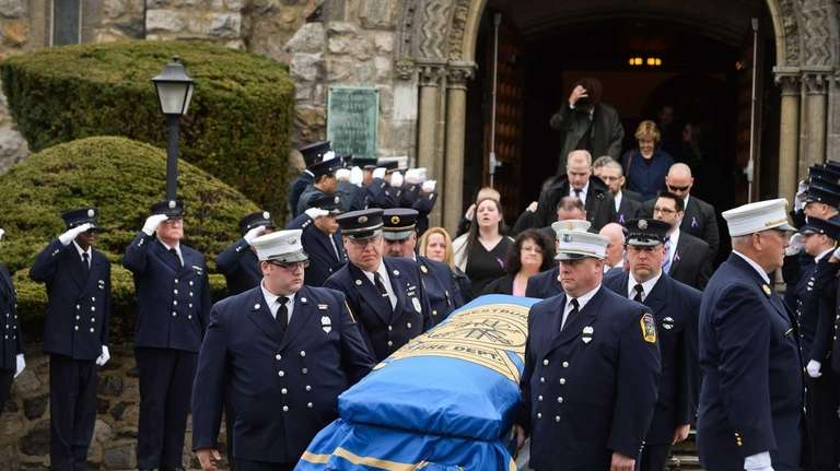 Firefighters carry the casket of volunteer firefighter Robert