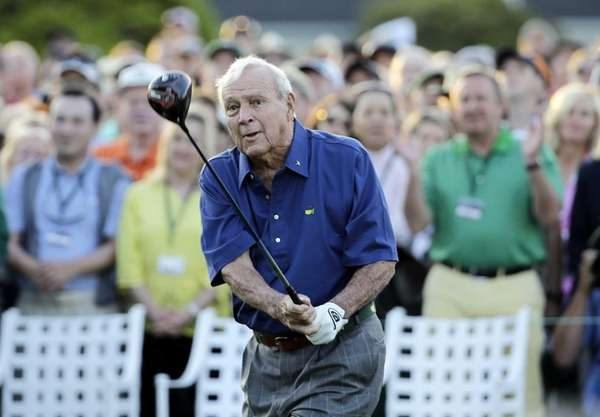 Arnold Palmer watches his tee shot for the
