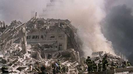 Firemen work in the rubble at the base