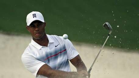 Tiger Woods hits out of a bunker at