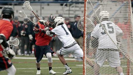 Manhasset's John Keogh (11) fights off the stick
