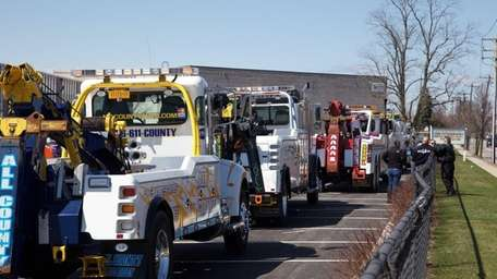 Tow trucks line up in a parking lot