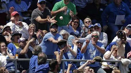 Fans vie for a foul ball hit by
