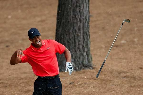 Tiger Woods throws his golf club after taking