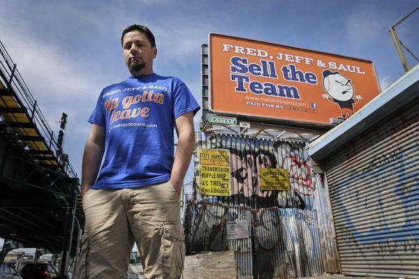 Gary Palumbo near a billboard criticizing the ownership