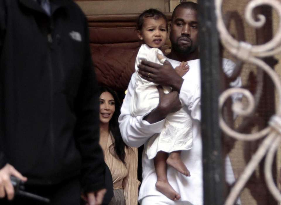 Kim Kardashian and husband Kanye West, holding their