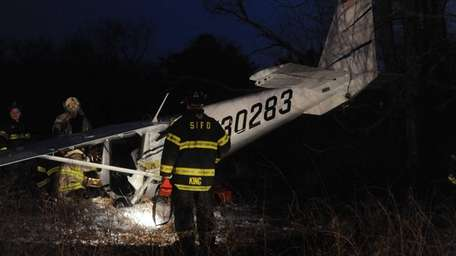 Emergency personnel investigate the scene after a plane