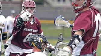 Garden City's Conor Muldoon points to celebrating teammate