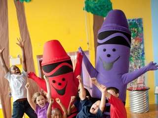 Children with Crayola's mascots at the Crayola Factory