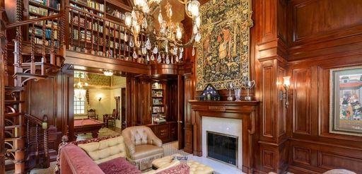 A library boasts floor-to-ceiling mahogany paneled walls and