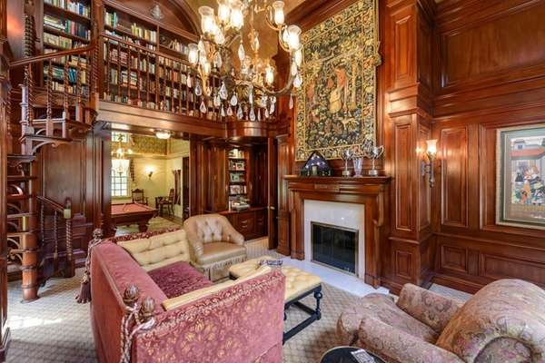 A library boasts floor-to-ceiling mahogany paneled walls and