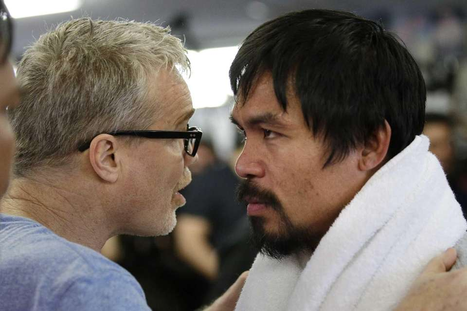 Manny Pacquiao, right, listens to his trainer, Freddie