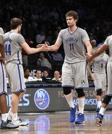 Brooklyn Nets center Brook Lopez low fives guard