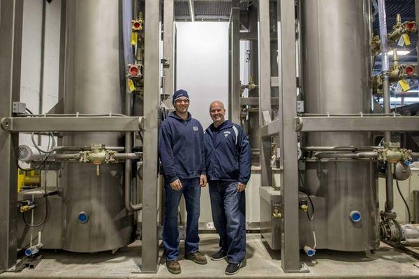 Arctic Glacier plant manager Brent Hill, left, stands
