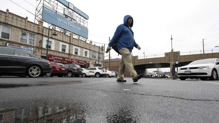 Pedestrians walk through wet roads as showers move