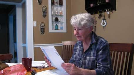 Carol Sykes with several years' worth of bills