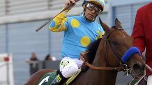 Victor Espinoza raises his whip as he and
