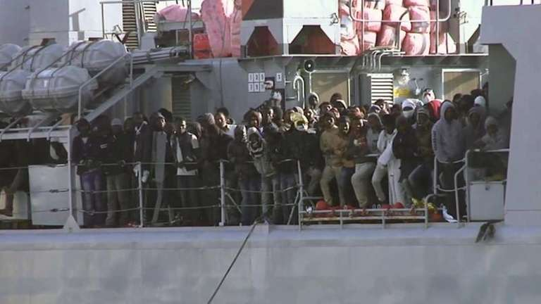 In this image from TV, migrants crowd at