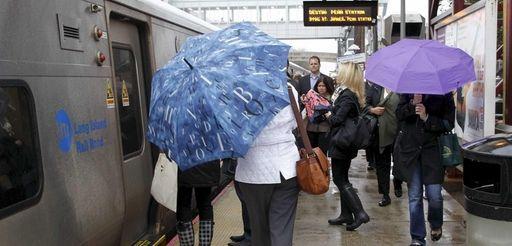 Commuters dodge raindrops at the Long Island Rail