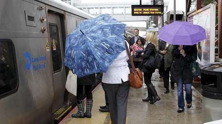 Commuters dodge raindrops at the Long Island Rail