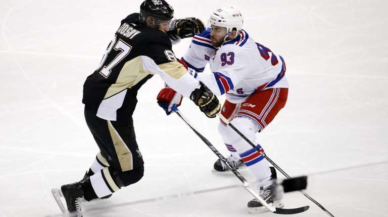 The Pittsburgh Penguins' Sidney Crosby (87) is checked