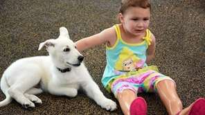 Three-year-old Sapphyre Johnson and 8-week-old German shepherd Lt.