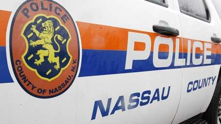 Nassau police vehicles sit behind the 5th precinct
