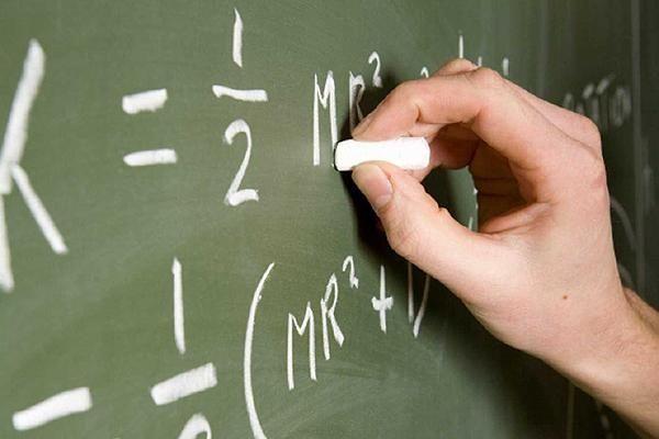 A teacher writing on a chalk board.