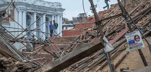 People stand on top of debris from a